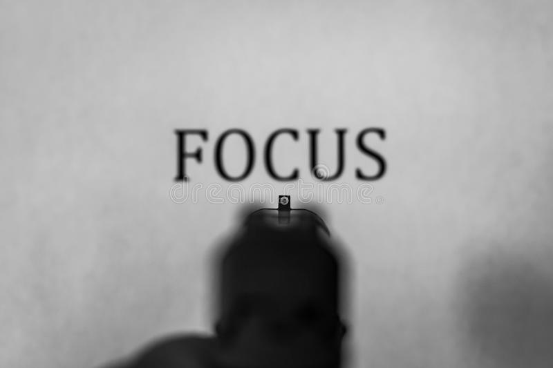 Handgun Sights - FOCUS. Handgun sights, pointing at the word FOCUS in the background stock photos