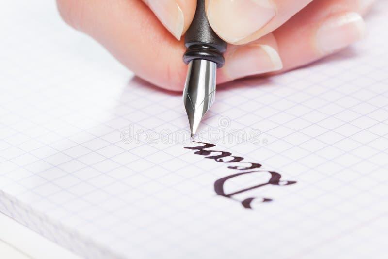 Handhandstil med reservoarpennan på den kvadrerade anteckningsboken arkivfoto