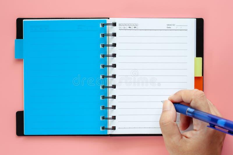 Handhandstil på en öppnad tom anteckningsbok med pennan på rosa backgr arkivbild