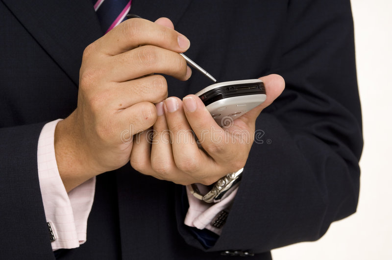 Handheld Computing. A businessman in a navy suit and pink shirt uses a handheld computer stock photos