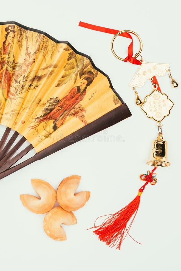Handheld fan för traditionell kines med amuletten och förmögenhetkakor som isoleras på vit, kinesiskt begrepp för nytt år arkivfoton