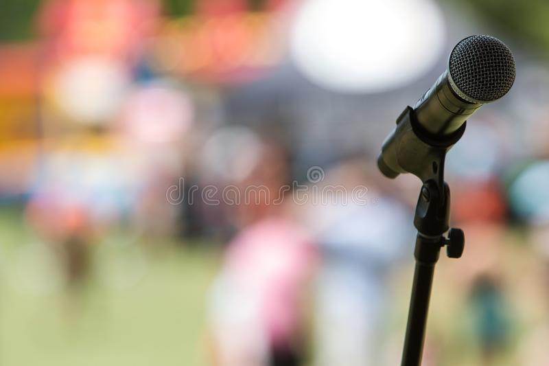 Handheld Mic Rests In Stand On Stage At Atlanta Festival. Closeup of handheld mic resting on mic stand on stage at festival stock photo