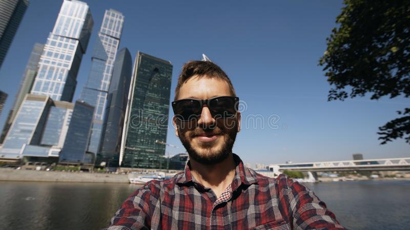 Happy tourist man having online video chat using his smartphone camera near international business center in Moscow stock photography