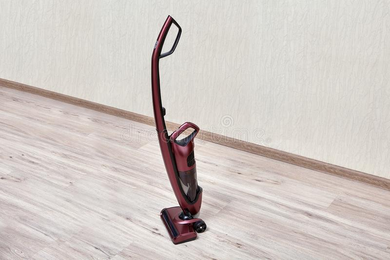 Upright red vacuum cleaner in empty room. Handheld vacuum cleaner with a separate small dust tank in an empty room royalty free stock photography