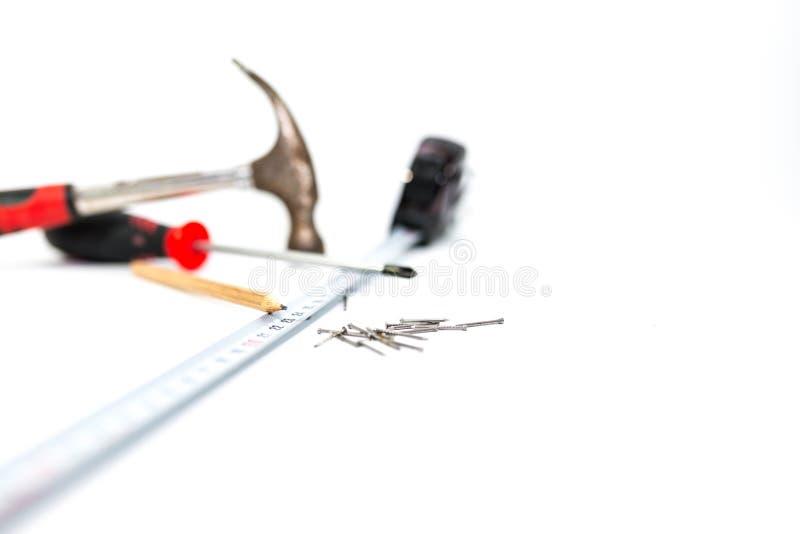 Handhjälpmedel på vit bakgrund, hammaren, skruvmejseln, linjalen, blyertspenna och spikar, grunt djup av fältet arkivbilder