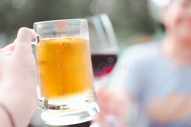 Handholding-Bierkrugzertrümmern mit Weinglas am Restaurant lizenzfreie stockbilder