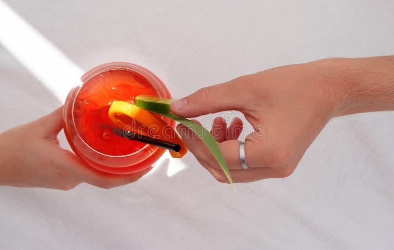 Handholding Cocktail Aperol spritz, andere Hand, die mit Blatt verziert lizenzfreie stockbilder