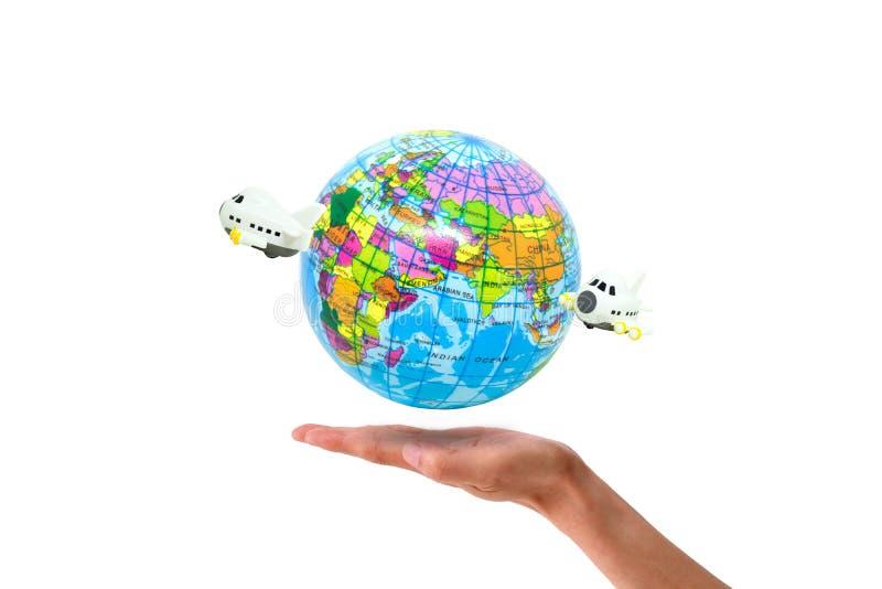 Handholding-Flugzeugfliegen um die Weltkugel lokalisiert auf weißem Hintergrund lizenzfreie stockfotos