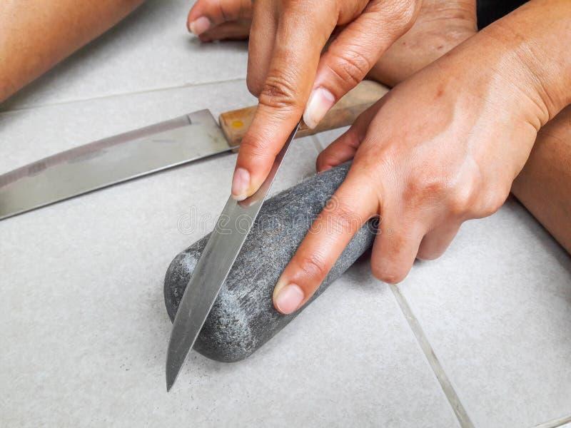Handholding schärfen Messer und Schleifstein lizenzfreie stockfotografie