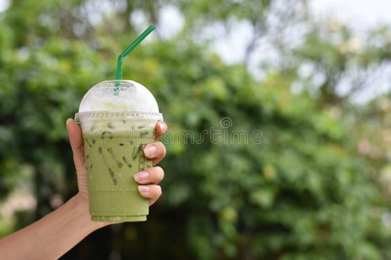 Handholding van bevroren groene thee in plastic glas stock fotografie