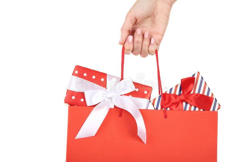 Handholdingeinkaufstasche mit Geschenkboxen stockfoto