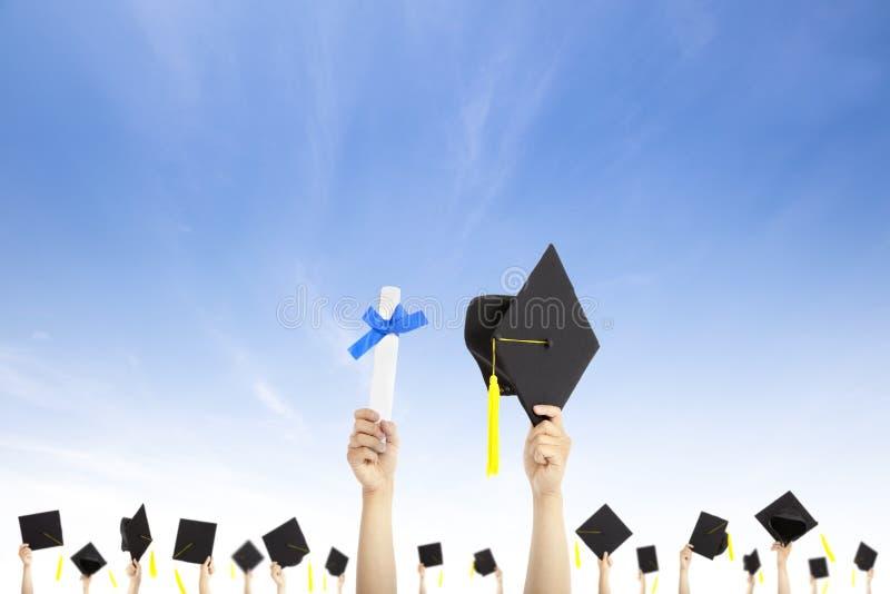 Handholdingstaffelunghüte und -diplom lizenzfreie stockbilder