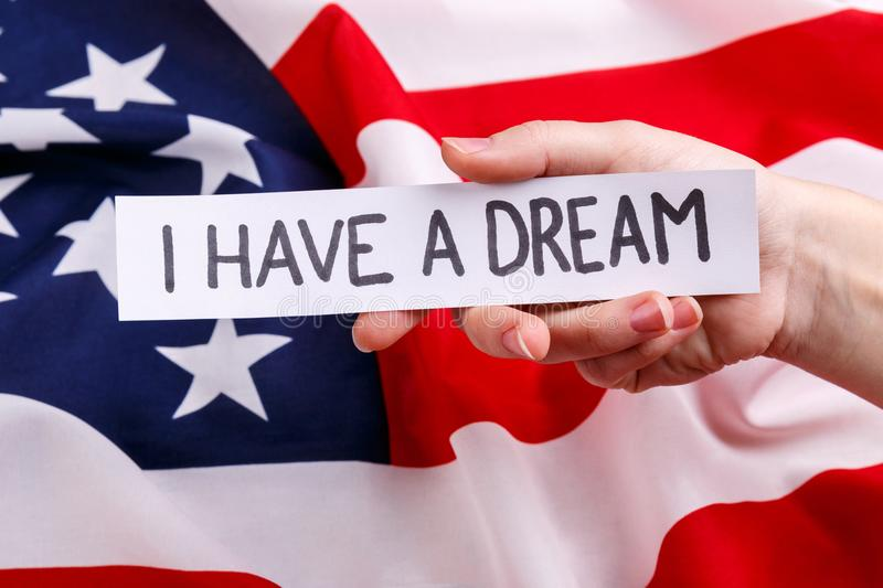 The handholds a piece of paper with the inscription Martin Luther King Jr. Day. The background of the American flag. The hand of a European man holds a piece of royalty free stock photo