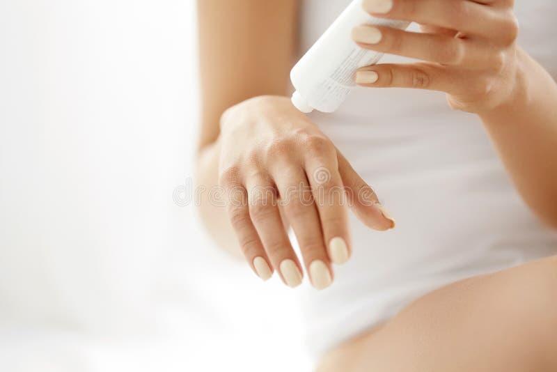 Handhudomsorg Closeup av kvinnliga händer som rymmer det kräm- röret arkivfoto
