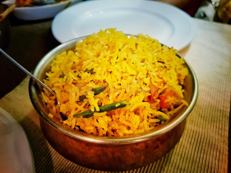 Handi biryni sweet pulao rice dish indian cuisine in a bowl on a table with white plates royalty free stock image