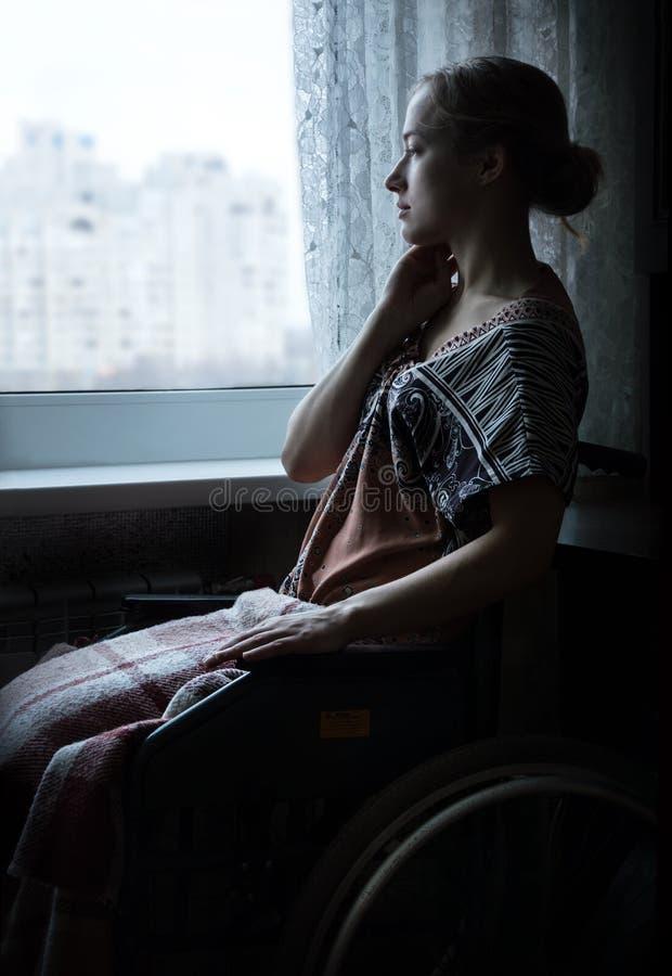 Handicapé dans la poussette par la fenêtre photographie stock libre de droits