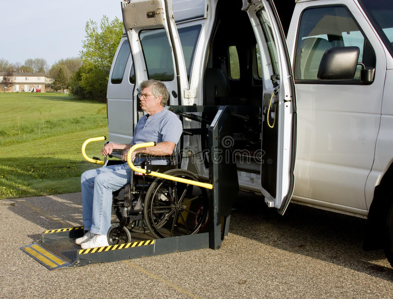Handicap wheelchair lift. Handicap van with a man in a wheelchair on a lift stock images
