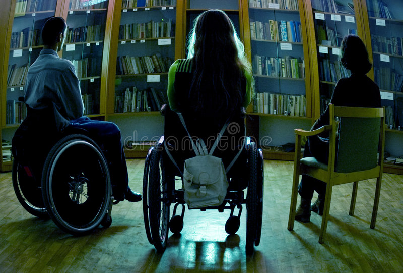 Handicapped. A view of the people watching television in a library, including a handicapped man and woman in wheelchairs stock photos