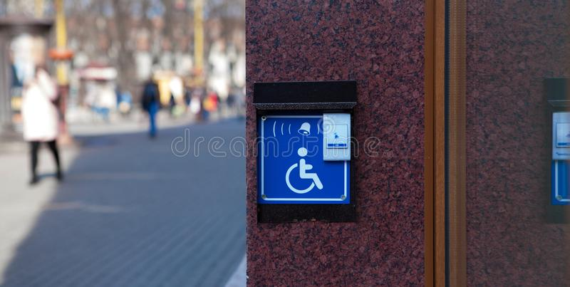 Handicapped access entrance pad mounted to a wall. Sign a button for a visa for people with disabilities.  royalty free stock photography