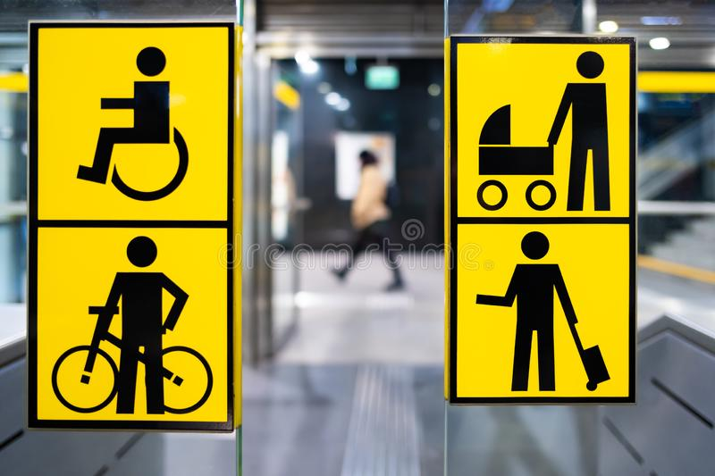 Handicapped, bicycle, stroller and big luggage yellow pictrogram in metro, information in public transport, blurred person in the. Background royalty free stock photo