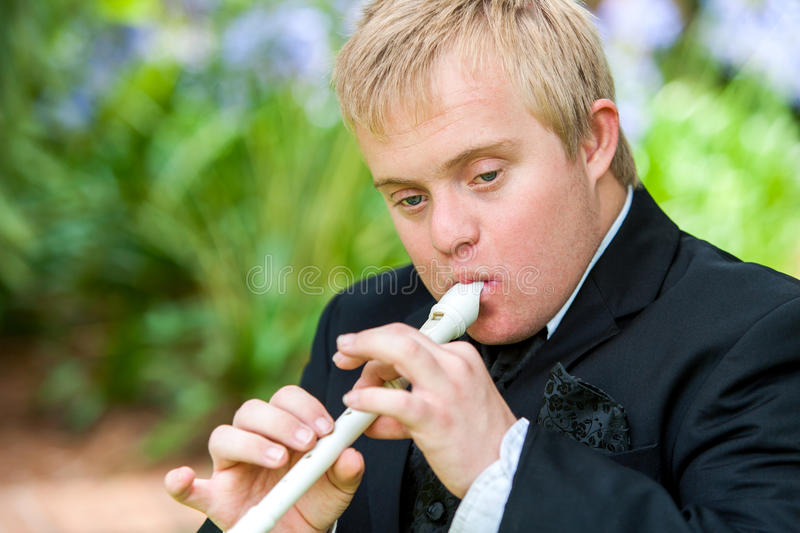 Handicapped boy playing block flute. royalty free stock photo