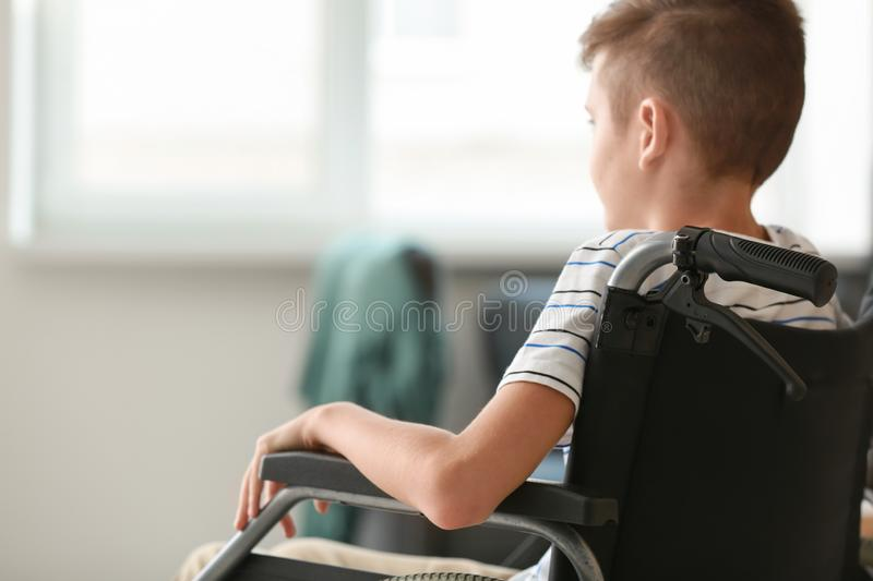 Handicapped boy in wheelchair at home stock photography