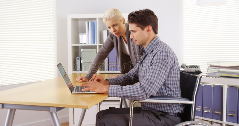 Handicapped businessman and colleague working in the office royalty free stock image