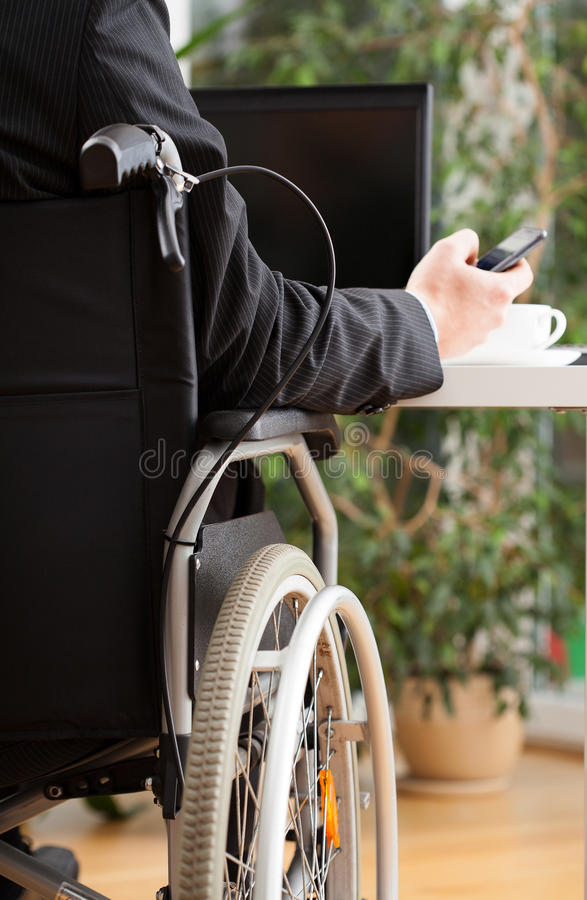 Handicapped businessman texting during work. Businessman on wheelchair texting during his work in office royalty free stock photography