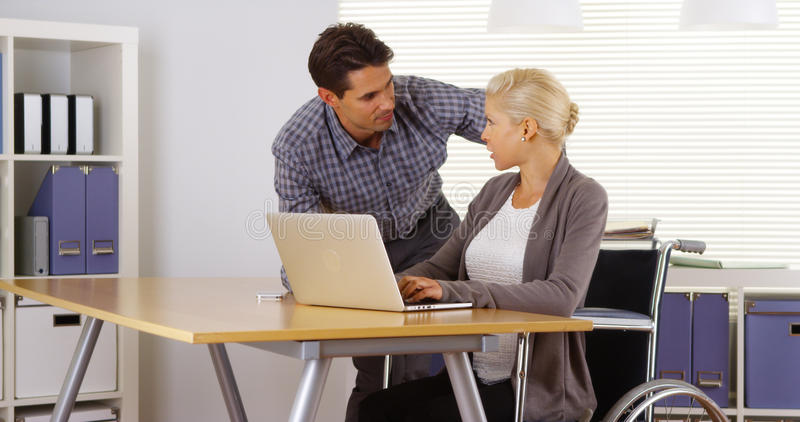 Handicapped businesswoman and colleague working together in office royalty free stock photos