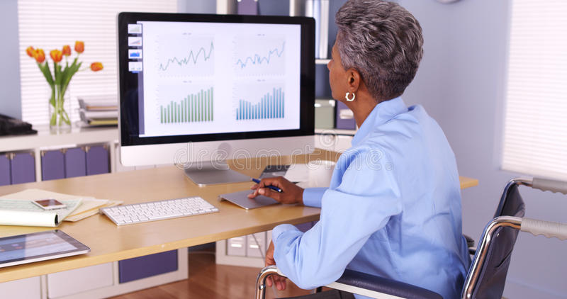 Handicapped businesswoman working at desk stock photo