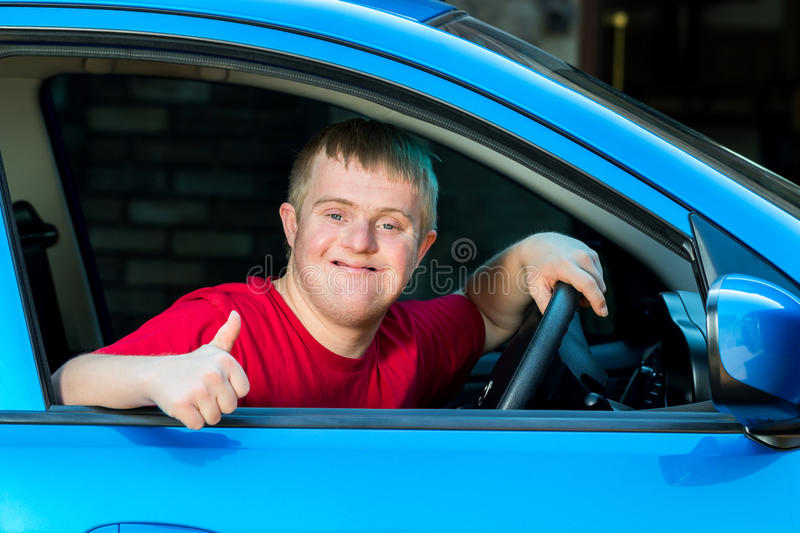 Handicapped car driver doing thumbs up. Close up portrait of young man with down syndrome sitting behind steering wheel in blue car stock image