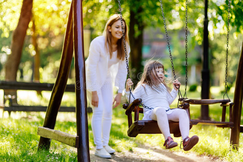 Handicapped child enjoying the swing. Outdoors with sister royalty free stock image