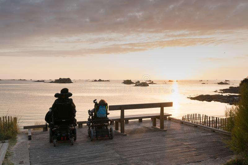 Handicapped couple in wheelchairs enjoy a beautiful ocean sunset together from a handicapped beach access viewpoint. Roscoff, Finistere / France - 21 August 2019 stock photography