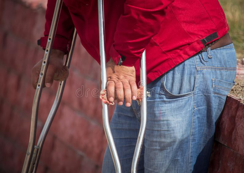 Handicapped with crutches in the hands of the street.  royalty free stock photography