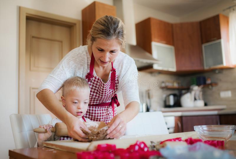 A handicapped down syndrome boy with his mother indoors baking. stock images