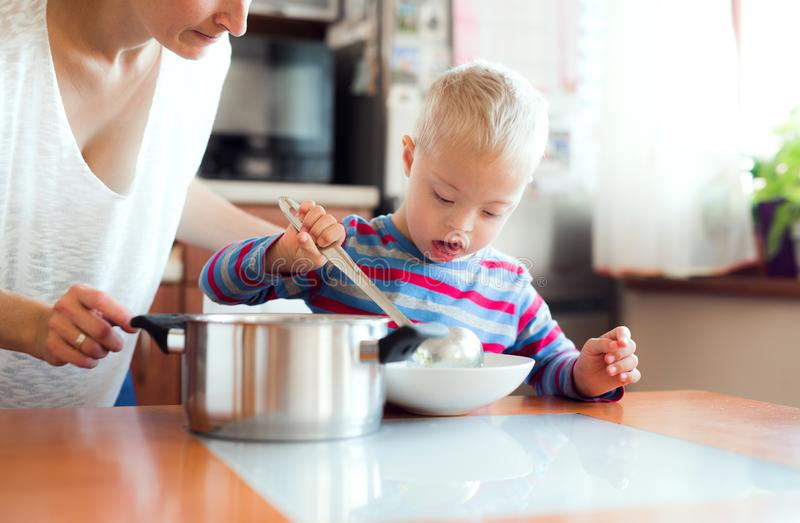A handicapped down syndrome boy pouring soup in a plate indoors, lunch time. A happy handicapped down syndrome boy with unrecognizable mother pouring soup in a royalty free stock photos