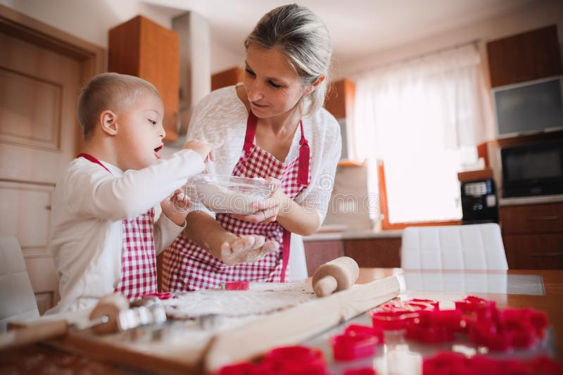 A handicapped down syndrome child with his mother indoors baking. A handicapped down syndrome child and his mother with checked aprons indoors baking in a stock image
