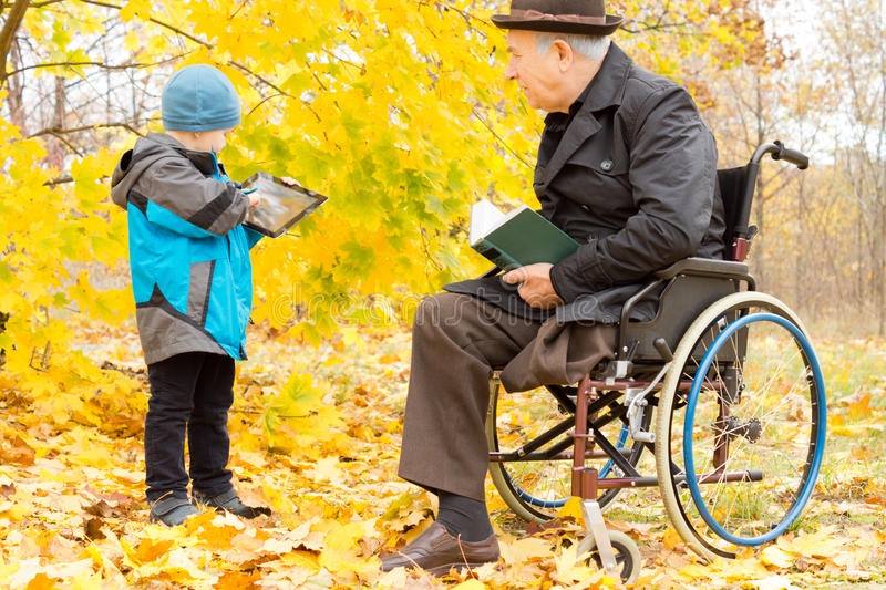 Handicapped elder man with one leg amputated. Handicapped elder men with one leg amputated sitting in a warm overcoat and hat in his wheelchair in a colourful royalty free stock photography