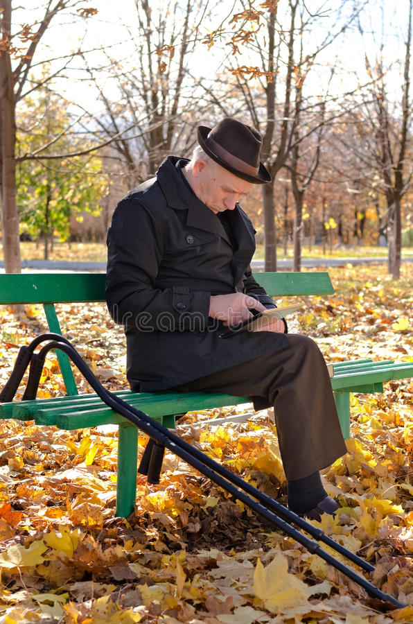Handicapped elderly man sitting in the park. On a wooden bench with his crutches alongside him browsing the internet on a tablet computer stock image