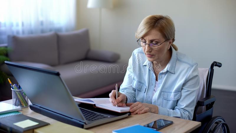 Handicapped grandmother making notes during online lesson home, senior student stock image