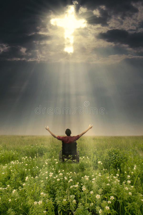 Handicapped male with a light cross in meadow. Handicapped male raising hands and looking at the light cross on the sky while sitting in a wheelchair royalty free stock photos