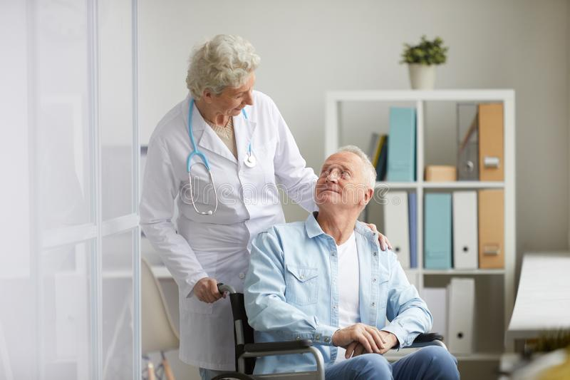 Handicapped Man in Clinic. Portrait of cqaring female doctor consulting handicapped elderly man, copy space royalty free stock images