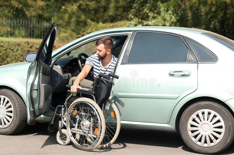 Handicapped man getting out of his car stock photography
