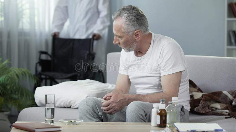 Handicapped man sitting on sofa at nursing home, male nurse bringing wheelchair stock image