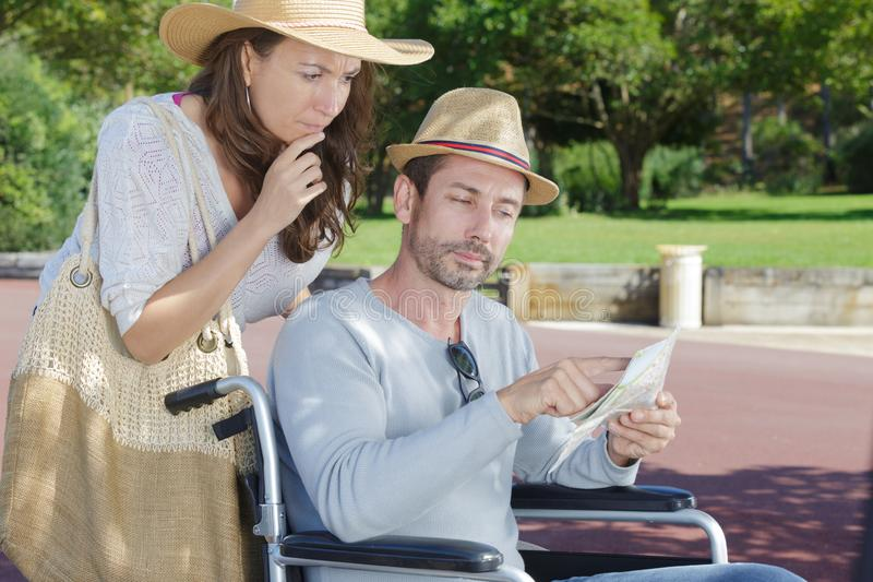 Handicapped man in wheelchair and girlfriend on holidays royalty free stock images