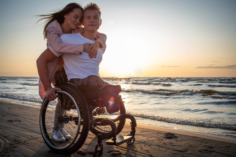 Handicapped man in wheelchair and his girlfriend on a beach at sunset royalty free stock images