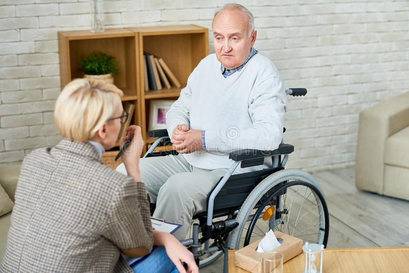 Handicapped Senior Man in Therapy. High angle portrait of disabled senior men in wheelchair sharing problems with psychiatrist during therapy session, copy space stock image