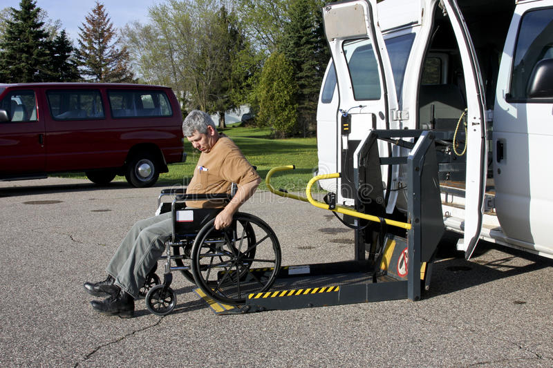 Handicapped van with lift. Handicapped person backing his wheelchair onto a lift van royalty free stock photography
