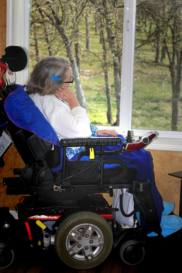 Handicapped woman looking out window stock photo
