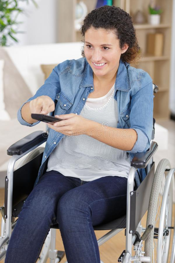 Handicapped woman pressing remote stock photos